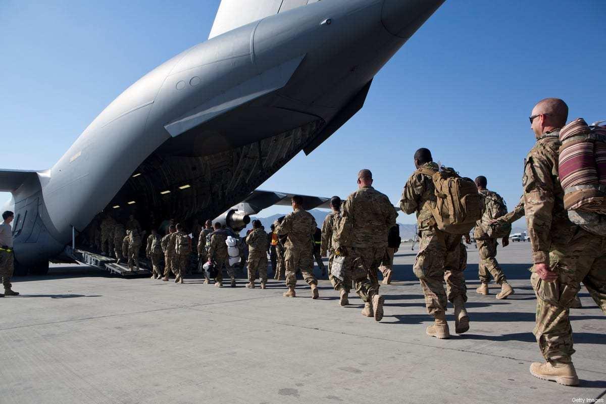 Soldados do Exército dos EUA caminham até seu avião de carga C-17 para a partida, em 11 de maio de 2013, na Base Aérea de Bagram, Afeganistão. [Robert Nickelsberg/Getty Images]