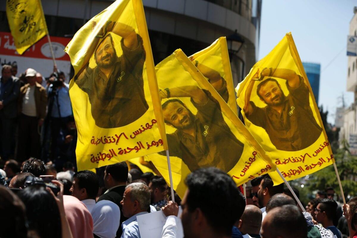 Manifestantes agitam bandeiras com um retrato do palestino Marwan Barghouti durante um manifestação na cidade de Ramallah, na Cisjordânia, em 17 de abril de 2017 [Abbas Momani/ AFP via Getty Images]