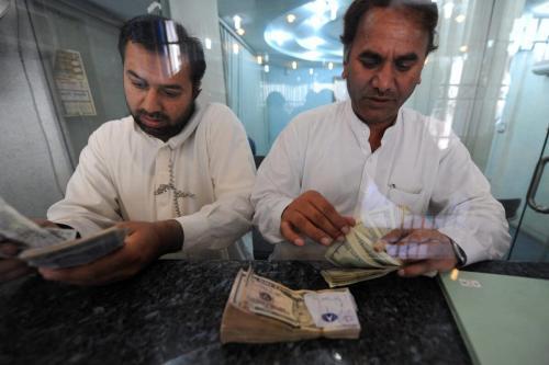 Negociadores contam dólares americanos e outras notas monetárias no mercado financeiro em 20 de abril de 2009 [AAMIR QURESHI / AFP via Getty Images]