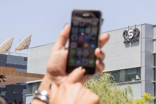 Uma israelense usa seu iPhone em frente ao prédio do grupo israelense NSO, em 28 de agosto de 2016, em Herzliya, próximo a Tel Aviv. [Jack Guez/ AFP / Getty Images]