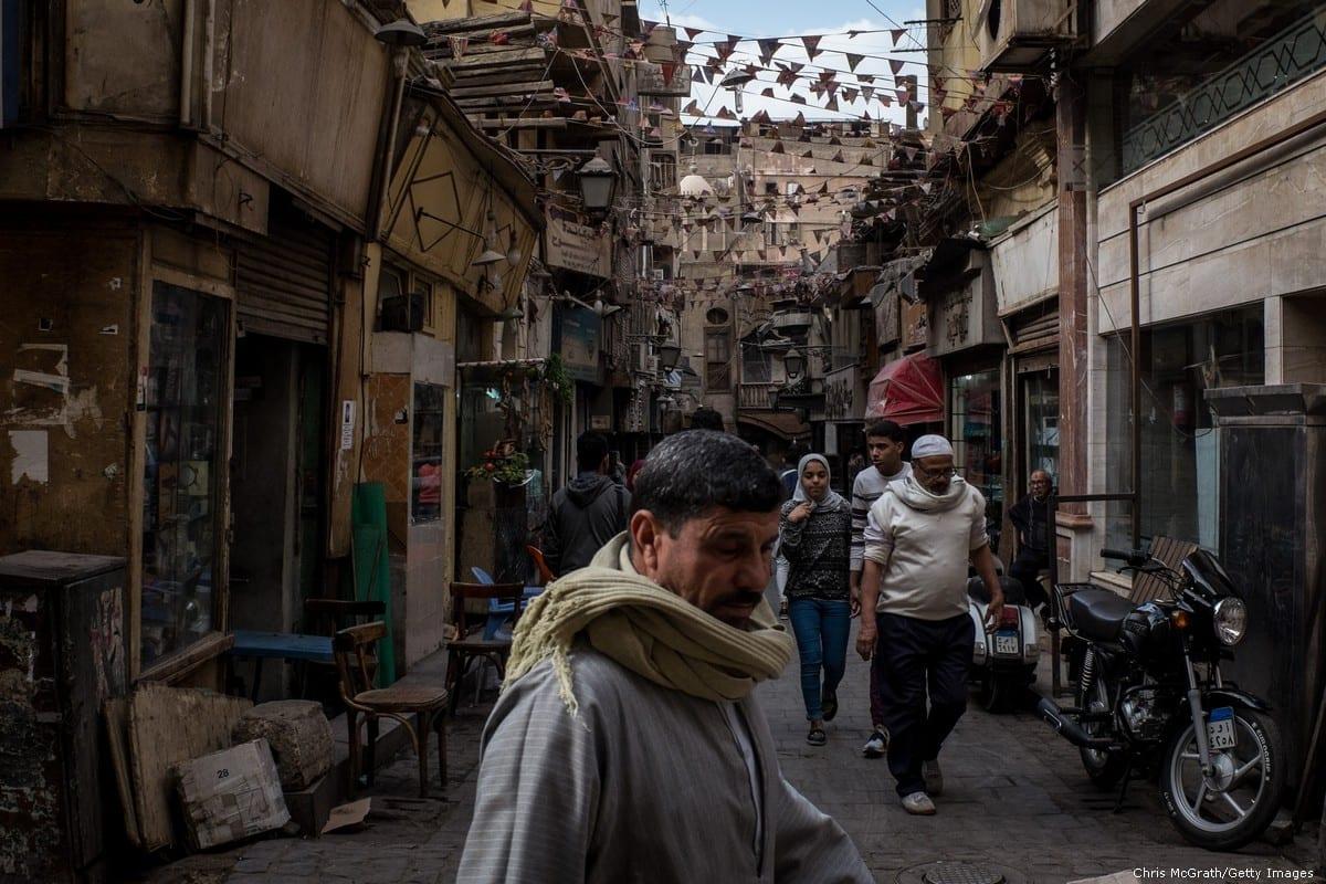 Pessoas são vistas fazendo compras em uma rua comercial no Cairo, Egito, em 14 de dezembro de 2016. [Chris McGrath/Getty Images]