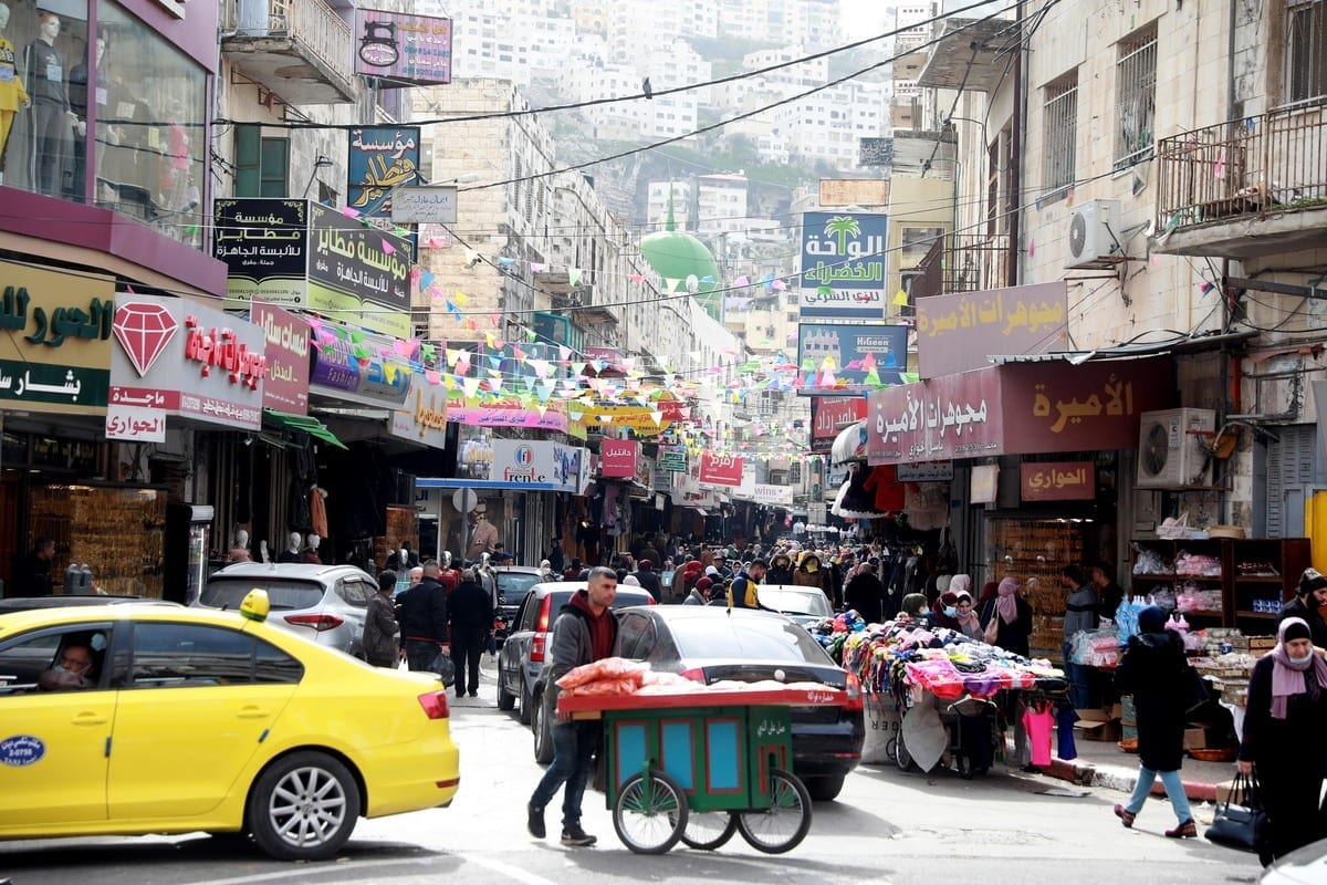 Palestinos compram em um mercado em Ramallah, Cisjordânia, em 30 de janeiro de 2021 [Issam Rimawi / Anadolu]