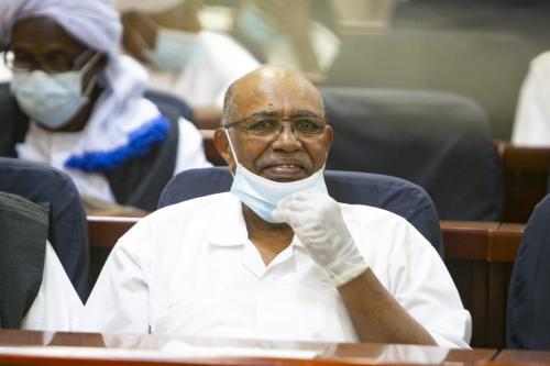 O presidente deposto do Sudão, Omar al-Bashir, aparece durante seu julgamento junto com outros sobre o golpe militar de 1989 que os levou ao poder, no tribunal especial estabelecido no Instituto de Treinamento de Oficial na capital, Cartum, em 2 de fevereiro de 2021. [Mahmoud Hjaj/Agência Anadolu]