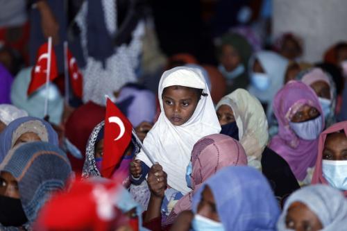 Mulheres e crianças etíopes segurando bandeiras turcas após uma instituição de caridade turca doar ajuda em Addis Abeba, Etiópia, em 17 de abril de 2021 [Minasse Wondimu Hailu/Agência Anadolu]