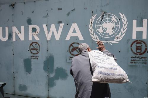 Um homem palestino em frente ao emblema da Agência de Assistência e Trabalhos da ONU (UNRWA), na Cidade de Gaza, em 31 de julho de 2018. [Said Khatib/AFP/Getty Images]
