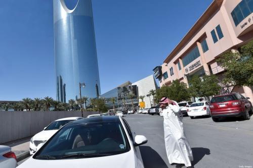"""O saudita Hussein ajusta sua tradicional """" shemagh"""" na cabeça antes de entrar no carro para começar o dia de trabalho para o Uber, na capital Riad, em 20 de janeiro de 2020. [Fayez Nureldine/ AFP via Getty Images]"""