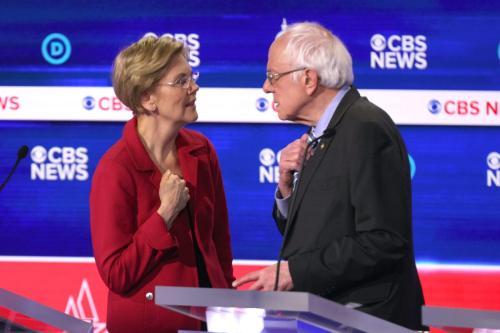 Os candidatos democratas à presidência, a senadora Elizabeth Warren (D-MA) (esq.) e o senador Bernie Sanders (I-VT) (dir.), interagem durante um intervalo no debate das primárias presidenciais democratas, em 25 de fevereiro de 2020, em Charleston, Carolina do Sul [Win McNamee/Getty Imagens]