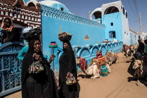 Mulheres egípcias da Núbia vendem souvenirs na vila de Gharb Suhail, perto de Aswan, no Alto Egito, cerca de 920 quilômetros ao sul da capital Cairo, em 5 de fevereiro de 2020 [Khaled Desouki/AFP via Getty Images]