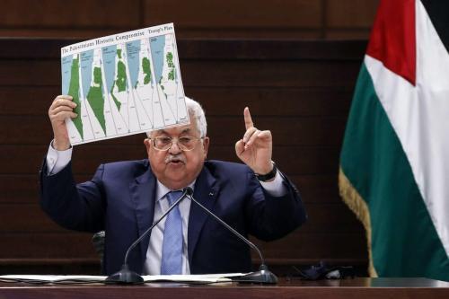 O presidente palestino Mahmud Abbas segura um cartaz mostrando mapas da Palestina histórica [Alaa Badarneh/ Pool/ AFP via Getty Images]