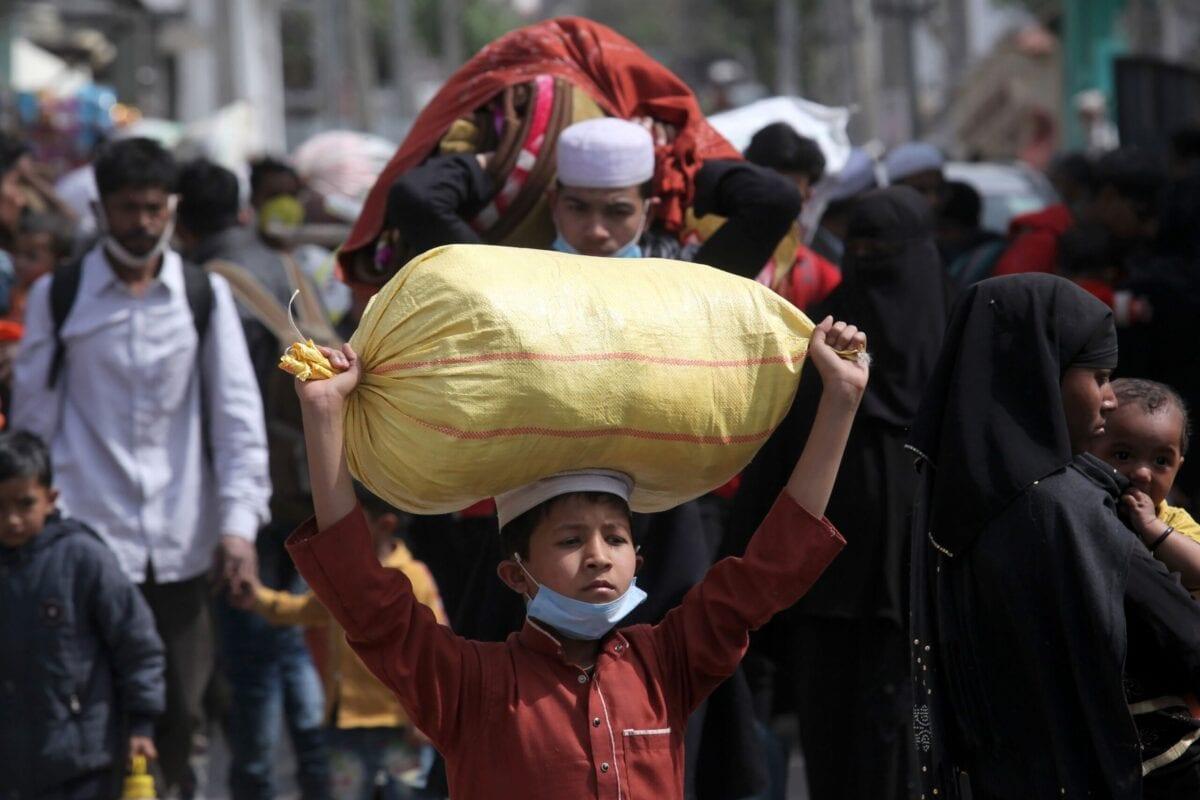 Cidadãos rohingyas carregam seus pertences ao deixar um campo de refugiados em Jammu, território disputado entre Índia e Paquistão, em 7 de março de 2021 [Rakesh Bakshi/AFP via Getty Images]