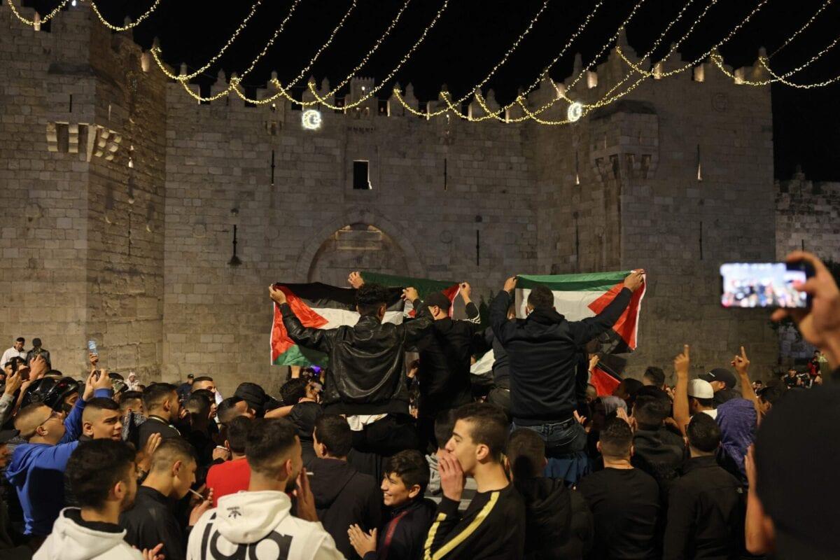 Palestinos exibem sua bandeira nacional em frente ao Portão de Damasco, na Cidade Velha de Jerusalém, 27 de abril de 2021 [Menahem Kahana/AFP via Getty Images]