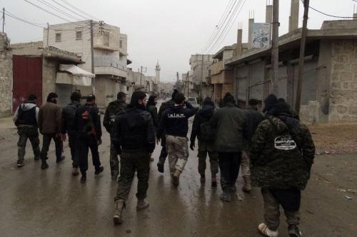 Combatentes da brigada de oposição síria Ahrar al-Sham caminham no bairro de Shiekh Lufti, na cidade de Aleppo, durante confrontos com forças do regime de Bashar al-Assad, em 27 de janeiro de 2014 [Baraa al-Halabi/AFP via Getty Images]