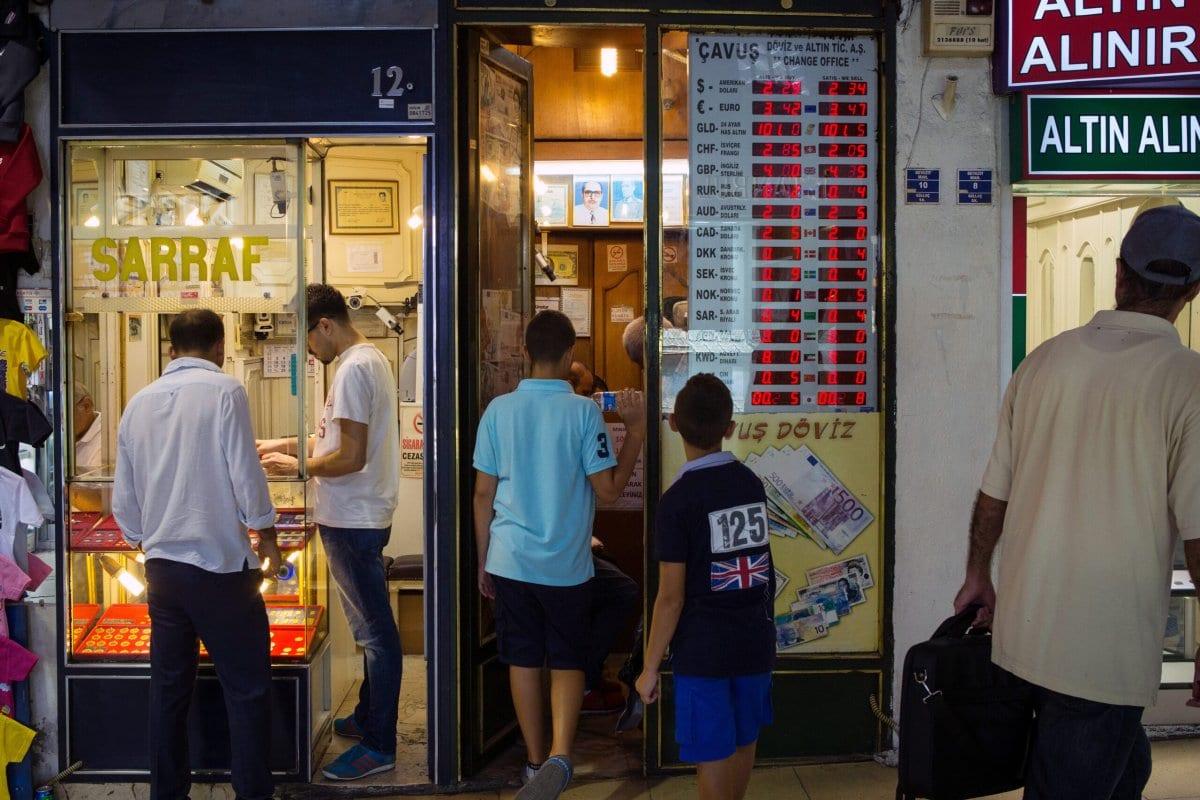 Clientes procuram joias de ouro em exposição na vitrine de uma loja enquanto outros fazem fila para usar uma agência de câmbio no Grand Bazaar's em Istambul, Turquia, em 15 de agosto de 2015. [Kerem Uzel / Bloomberg via Getty Images]