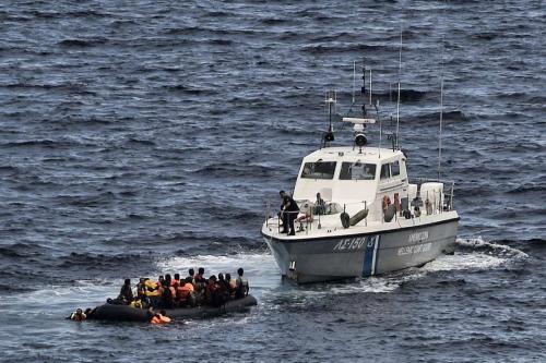 Uma guarda costeira helênica resgata refugiados e migrantes em um bote enquanto eles tentavam chegar à ilha grega de Lesbos atravessando o mar Egeu desde a Turquia, em 29 de setembro de 2015 [ARIS MESSINIS/AFP/Getty Images]