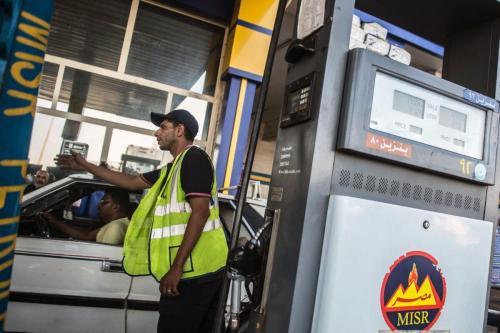 Um trabalhador gesticulando para os carros se moverem enquanto outros abastecem em um posto de gasolina no Cairo, Egito, em 29 de junho de 2017 [Khaled Desouki/Getty Images]