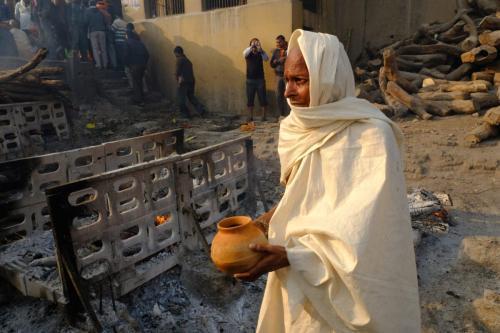 Monge hindu carrega uma tigela de água para derramar sobre as cinzas de um homem morto após a conclusão do ato de cremação em 28 de janeiro de 2018 [Kaveh Kazemi / Getty Images]