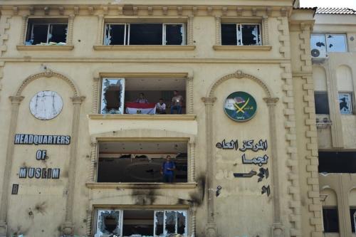 Manifestantes egípcios estão no quartel-general queimado da Irmandade Muçulmana no Cairo, Egito, em 1º de julho de 2013 [Khaled Desouki/AFP/Getty Images]