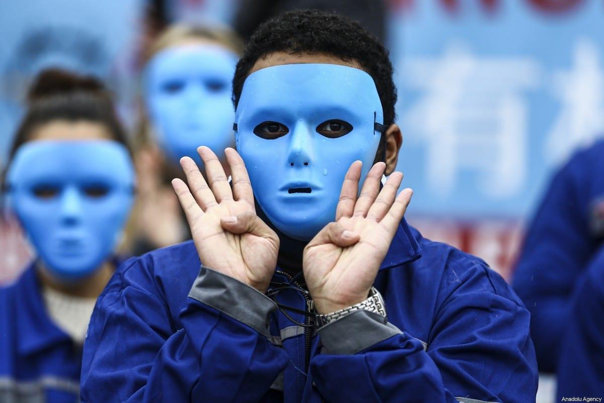 Manifestantes usam máscaras durante um protesto contra as políticas e opressões do governo chinês contra os uigures em frente à embaixada chinesa em Berlim, Alemanha, em 23 de janeiro de 2021 [Abdulhamid Hoşbaş/Agência Anadolu]