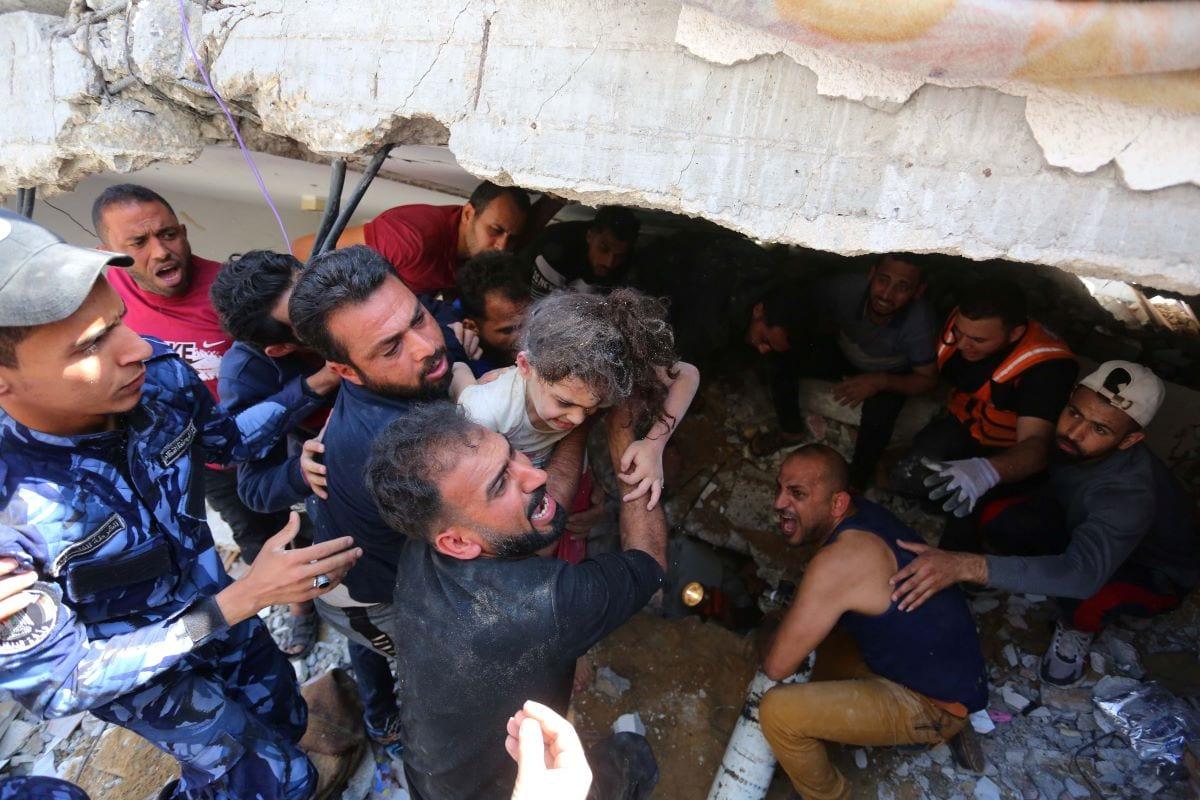 Riad Eshkuntana, que perdeu sete pessoas de sua família em bombardeio de Israel, faz o resgate da única filha sobrevivente, Suzi, de 6 anos. [Ashraf Amra/ Agência Anadolu]