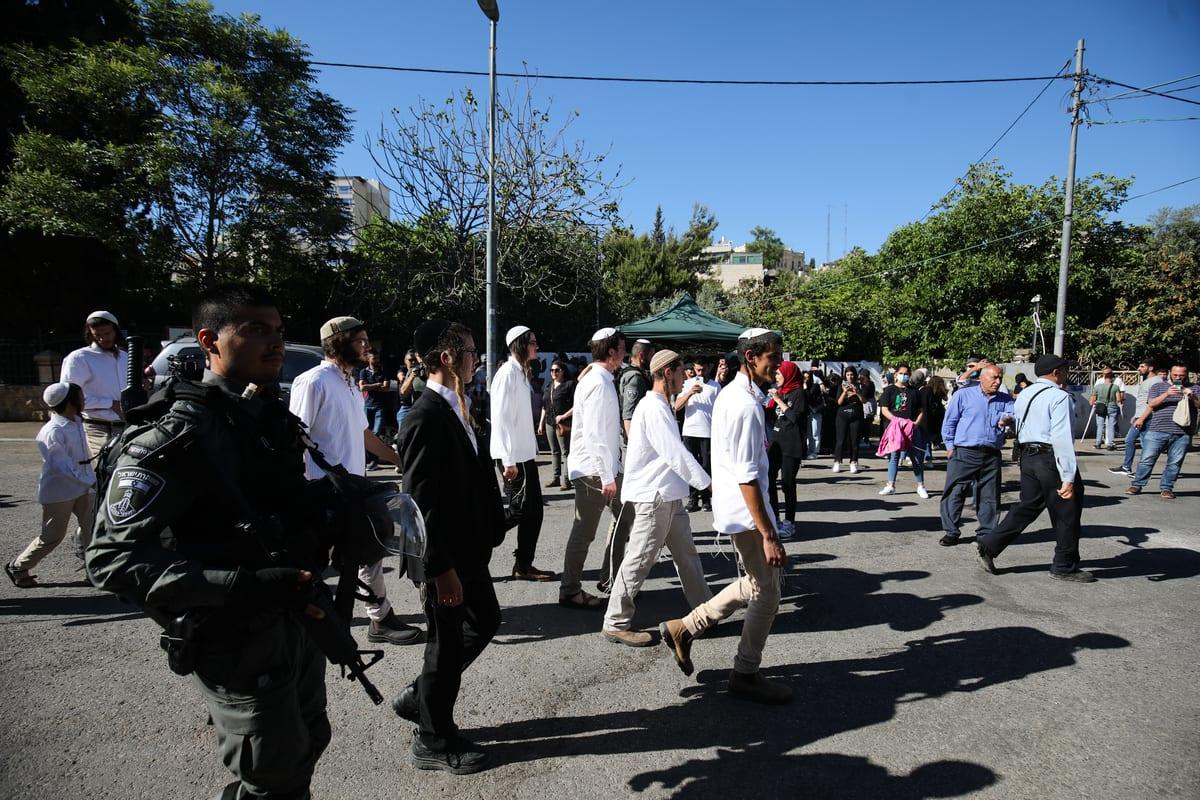 Colonos e forças israelenses marcham por Jerusalém ocupada, em meio a protestos palestinos, 15 de maio de 2021 [Mostafa Alkharouf/Agência Anadolu]