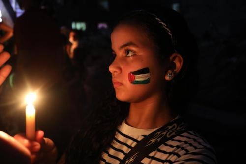 Crianças palestinas acendem velas em memória da família Abu Hattab, morta pelos bombardeios israelenses contra a Faixa de Gaza, 23 de maio de 2021 [Ashraf Amra/Agência Anadolu]