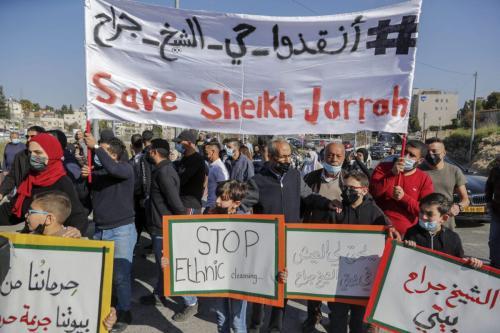 Ativistas palestinos, israelenses e estrangeiros exibem cartazes durante um protesto contra os assentamentos ilegais de Israel nos territórios palestinos ocupados, no bairro de Sheikh Jarrah, em Jerusalém, 19 de março de 2021 [Ahmad Gharabli/AFP/Getty Images]