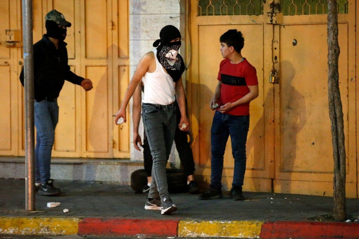 Jovens palestinos se preparam para atirar pedras durante confrontos com forças de segurança israelenses no centro da cidade ocupada de Hebron, na Cisjordânia, em 25 de abril de 2021 [Hazem Bader/AFP via Getty Images]