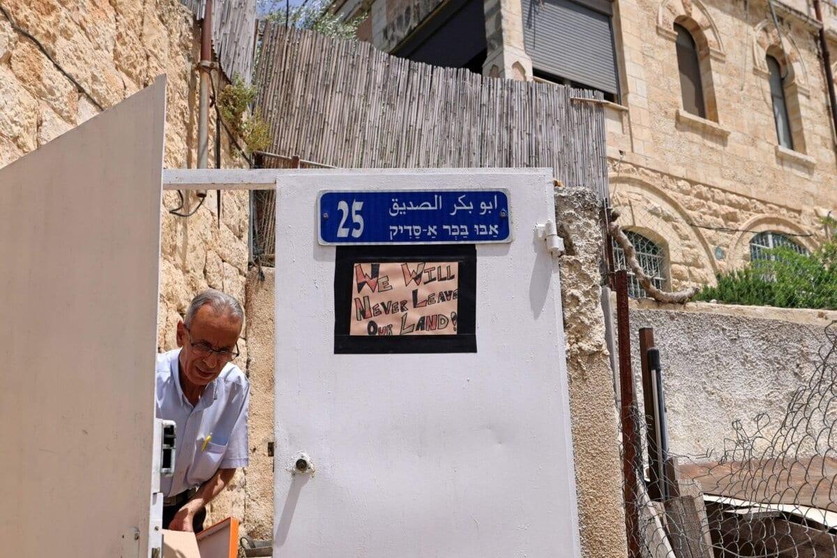 Um pôster contra as ordens de despejo israelenses é visto pendurado no portão de uma casa palestina no bairro de Sheikh Jarrah, em Jerusalém Oriental ocupada, em 5 de maio de 2021 [Emmanuel Dunand/AFP via Getty Images]