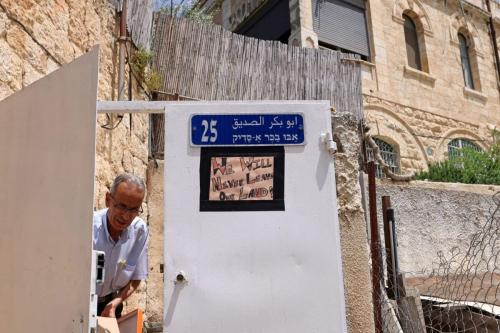 Cartaz protesta contra ordens de despejo da ocupação israelense, no portão de uma casa palestina em Sheikh Jarrah, Jerusalém Oriental, 5 de maio de 2021 [Emmanuel Dunand/AFP via Getty Images]