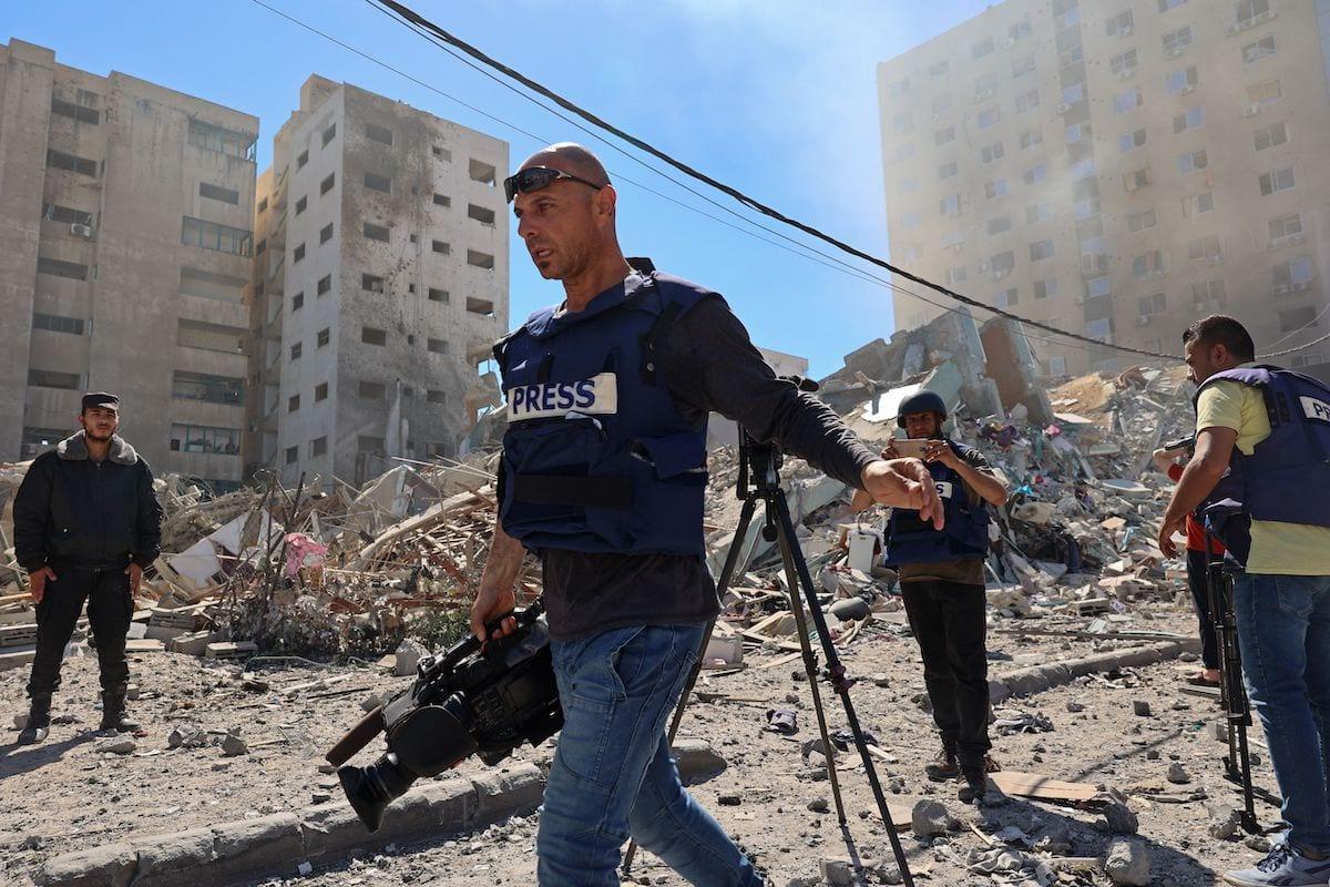 Jornalistas palestinas registram a destruição da Torre al-Jalaa, que abrigava escritórios da imprensa internacional, após ataques aéreos israelenses, na Faixa de Gaza, 15 de maio de 2021 [Mohammed Abed/AFP via Getty Images]