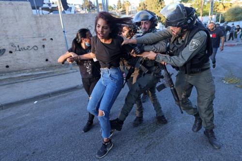 Forças de segurança israelenses tentam deter uma mulher palestina no bairro de Sheikh Jarrah, em Jerusalém oriental, em 15 de maio de 2021 [Emmanuel Dunand/AFP via Getty Images]