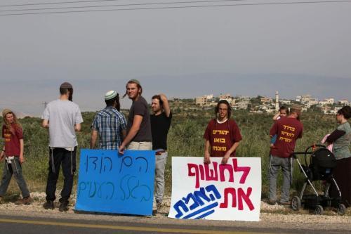 Ativistas de direita israelenses de assentamentos próximos protestam em a estrada principal que leva à aldeia palestina de Duma na Cisjordânia ocupada por israelenses em 5 de abril de 2016 [Menahem Kahana/ AFP via Getty Images]