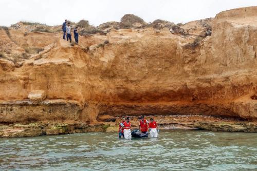 Membros do Crescente Vermelho Líbio recuperam o corpo de um migrante afogado na costa de Tajoura, a leste da capital Trípoli, em 3 de julho de 2018 [Mahmud Turkia/AFP via Getty Images]