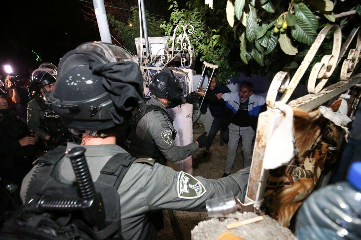 Forças israelenses arrombam um portão de uma família palestina durante manifestação contra a ordem israelense de expulsar residentes locais de suas casas, no bairro de Sheikh Jarrah, Jerusalém Oriental ocupada, 6 de maio de 2021 [Mostafa Alkharouf/Agência Anadolu]
