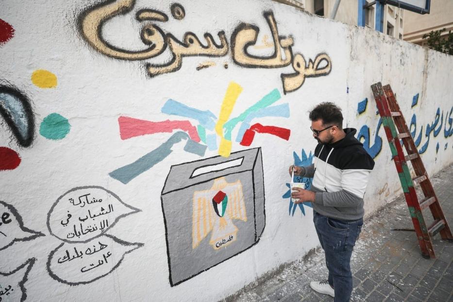 Artista palestino pinta um grafite relacionado às eleições em uma parede antes das eleições para o Conselho Legislativo Palestino na Cidade de Gaza, Gaza, em 24 de março de 2021 [Mustafa Hassona/Agência Anadolu]
