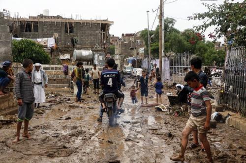 Pessoas são vistas em meio à lama em ruas destruídas, atingidas por uma enchente devido à forte chuva em Sanaa, Iêmen, em 7 de agosto de 2020 [Mohammed Hamoud/Agência Anadolu]