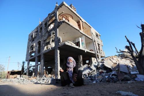 Uma senhora palestina senta-se em frente às ruínas de uma casa destruída pelos recentes bombardeios israelenses na Faixa de Gaza, em 7 de junho de 2021 [Ashraf Amra/Agência Anadolu]