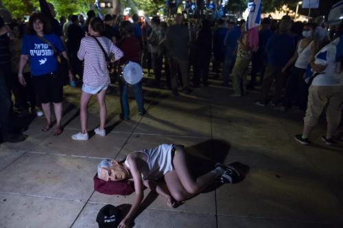 Mulher israelense com uma máscara do primeiro-ministro israelense, Benjamin Netanyahu, deita-se no chão durante um protesto em apoio a um governo de unidade para expulsar Netanyahu do cargo em 31 de maio de 2021 em Tel Aviv, Israel [Amir Levy/Getty Images]