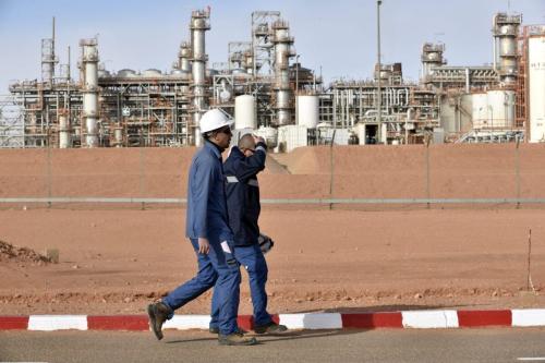Dois trabalhadores caminham na usina de gás em In Amenas, Argélia, em 16 de janeiro de 2018 [Ryad Kramdi/AFP via Getty Images]