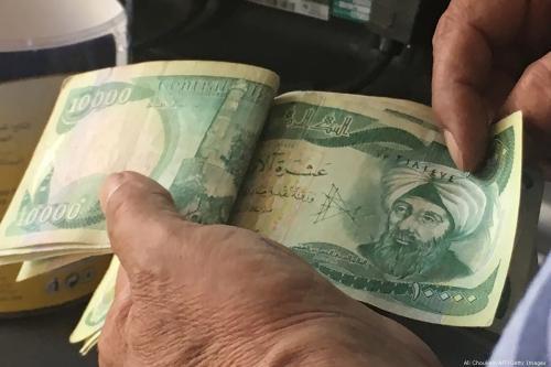Um iraquiano conta suas notas de dinar, em 22 de junho de 2017 [Ali Choukeir/AFP/Getty Images]