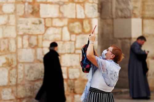 Uma visitante usando uma máscara, como proteção ao coronavírus, na entrada da Igreja do Santo Sepulcro na Cidade Velha de Jerusalém, em 9 de março de 2020 [Reuters/Ronen Zevulun]