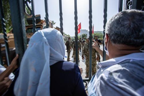 Forças de segurança da Tunísia protegem o Parlamento enquanto apoiadores e opositores se reúnem em frente ao prédio depois que o presidente tunisiano Kais Saied anunciou ter assumido plenamente a autoridade executiva, além de suspender o Parlamento em Tunis, Tunísia, em 26 de julho de 2021 [Nacer Talel/Agência Anadolu].