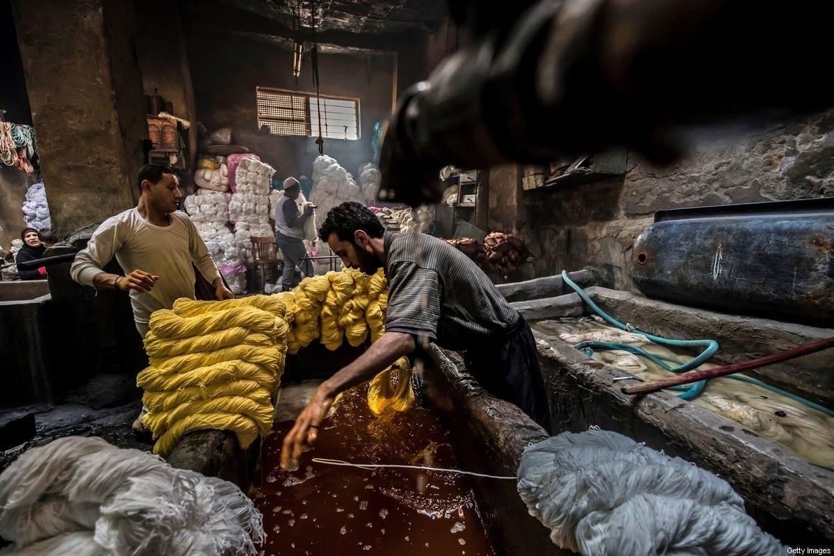 O Egito é um dos 10 piores países do mundo para trabalhadores, diz a ITUC. Trabalhadores tingem fios em uma cuba em uma oficina tradicional de tingimento à mão no distrito centenário de Darb al-Ahmar, capital egípcia Cairo, em 21 de janeiro de 2020 [Khaled Desouki/ AFP via Getty Imagens]