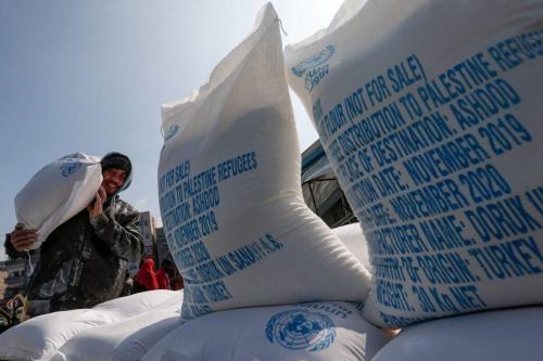 Um homem palestino carrega nos ombros sacos de farinha recebidos de um centro de distribuição da UNRWA no campo de refugiados de Jabalia, no norte da Faixa de Gaza, em 29 de janeiro de 2020 [Mahmud Hams/AFP via Getty Images]