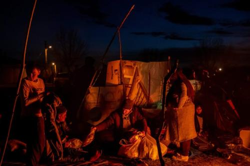 Um homem entrega um pacote de ajuda aos refugiados do Afeganistão em um acampamento onde refugiados e migrantes de vários países esperam na costa turca do rio Evros para cruzar de barco para a Grécia, em 03 de março de 2020, em Edirne, Turquia [Chris McGrath/Getty Images]