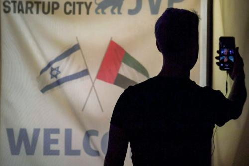 Um membro de uma delegação de tecnologia israelense usa seu telefone em uma videochamada durante uma reunião noturna com colegas dos Emirados em um hotel em Dubai, em 25 de outubro de 2020 [Karim Sahib/AFP/Getty Images]