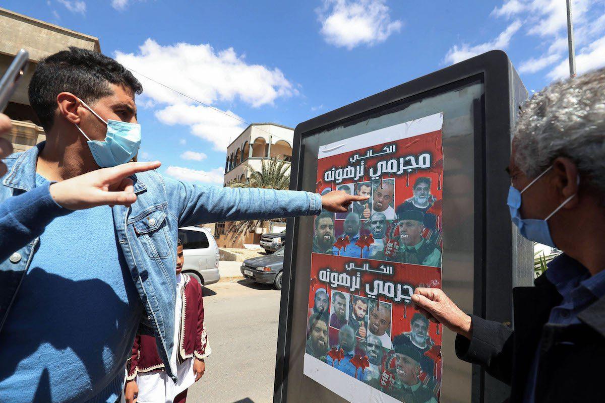 Cartaz com os dizeres 'al-Kani, criminosos de Tarhuna' denuncia os líderes de uma milícia que aterrorizou a região, durante o funeral de doze mortos encontrados em covas coletivas na cidade, 80 km a sudeste de Trípoli, capital da Líbia, 26 de março de 2021 [Mahmud Turkia/AFP via Getty Images]