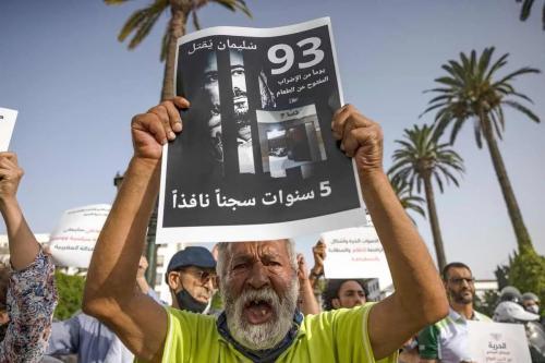 Um ativista marroquino segura uma bandeira com a imagem do jornalista marroquino Soulaimane Raissouni, em 10 de julho de 2021, na capital Rabat, exigindo sua libertação [FADEL SENNA/AFP via Getty Images]
