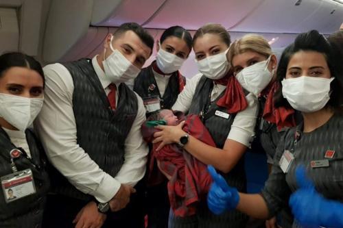 Tripulação posa com um bebê que nasceu a bordo do voo de evacuação da Turkish Airlines Dubai-Birmingham, a 10 mil metros de altitude, em 28 de agosto de 2021 [Turkish Airlines/Agência Anadolu]