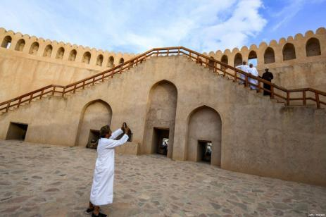 Um homem tira fotos de visitantes no topo de uma escadaria do Forte de Nizwa, uma fortificação do século 17 na cidade de mesmo nome, cerca de 160 quilômetros a sudoeste da capital Mascate [Giuseppe Cacace/AFP via Getty Images]